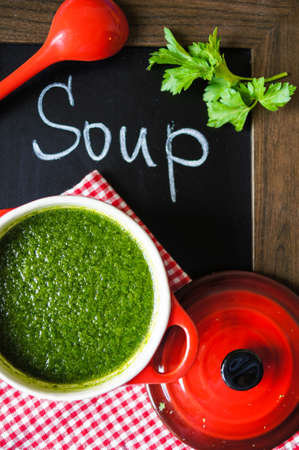 Spinach cream soup on the wooden table. Selective focus photo