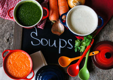 Different kinds of soups - sprinach soup, french onion cream-soup and carrot cream-soup on the table Imagens