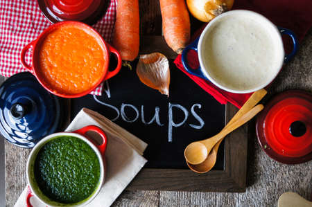 Different kinds of soups - sprinach soup, french onion cream-soup and carrot cream-soup on the table photo