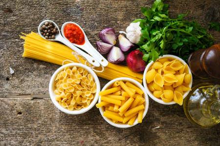 kinds: Different kinds of italian pasta, like a fusilli, farfalle, spaghetti and penne pasta