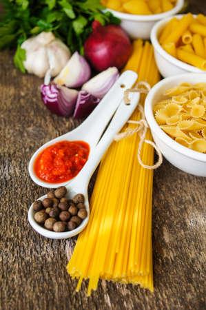 Different kinds of italian pasta, like a fusilli, farfalle, spaghetti and penne pasta photo