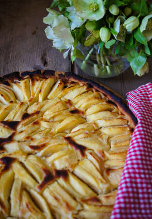 pastrie: French apple tart on the old rustic table with flowers and napkin