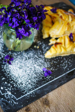 French apple tart on the old rustic table with flowers and napkin