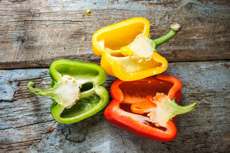 Fresh vegetables, different colors of bell pepper on the wooden background