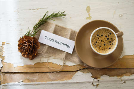 good morning: Cup of black coffee and first spring snowdrop flowers on the old table Stock Photo