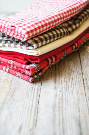 dishtowel: Stack of colorful dish towels on wooden table. Stock Photo