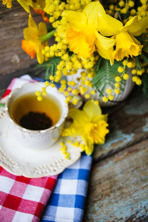 jonquil: Easter time, spring flowers and cup of tea on the old wooden table