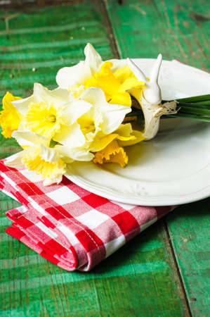 Spring festive easter dining table setting with yellow daffodil flowers,  napkins and vintage cutlery on a wooden board photo
