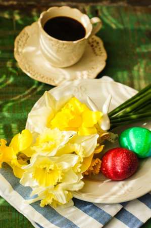 vintage cutlery: Spring festive easter dining table setting with yellow daffodil flowers,  napkins and vintage cutlery on a wooden board