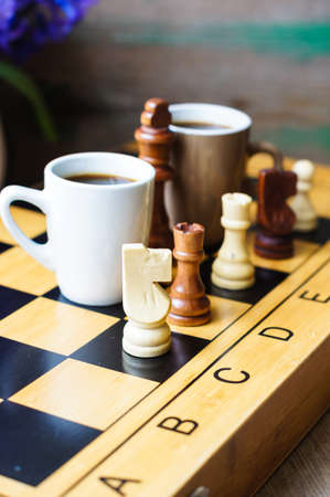 board game: Cup of coffee on the chess board and first spring flowers Scylla Stock Photo