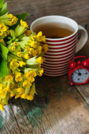 Tea time, red stripped cup of tea, spring flowers and Have a nice day note photo