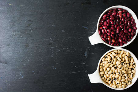 Different types of beans in the white bowls on the black stone background photo