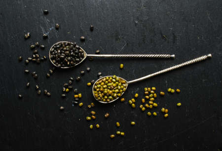 Different types of beans in the vintage spoons on the black stone background photo