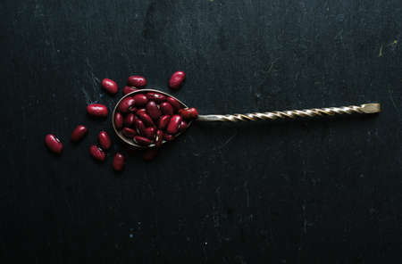 red gram: kidney beans in the vintage spoon on the black background Stock Photo