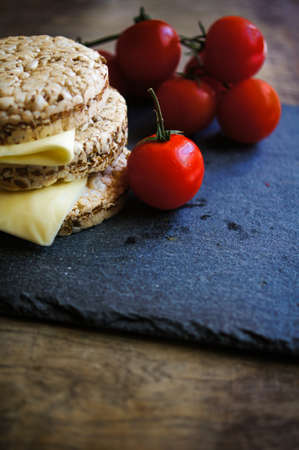rustic food: Healthy food, diet bread, cheese and cherry tomatoes on the rustic table