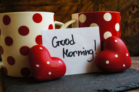 good morning: Red tea cup with tea and lemon on the old wooden background with note