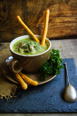 Chicken soup with bread sticks on the rustic kitchen