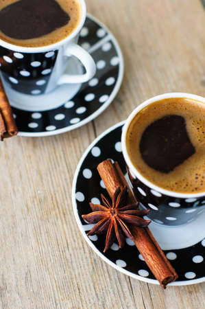turkish coffee: Black and white dots cup of coffee on the old wooden table with coffee beans, cinnamon sticks and anise star