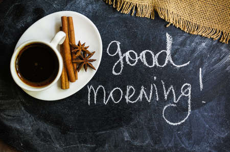 Coffee time, cup of black coffee and cinnamon and anise spices, Good morning note