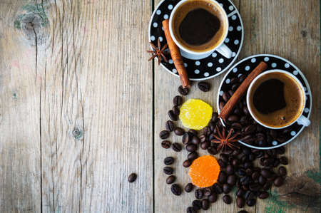 frijoles rojos: Black and white dots cup of coffee on the old wooden table with coffee beans, cinnamon sticks and anise star