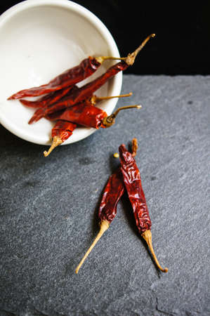 cousin: dried hot red chilies on textured wood Stock Photo