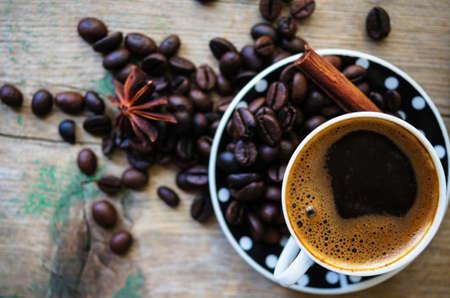 frijoles rojos: Blanco y negro puntos taza de caf� en la vieja mesa de madera con los granos de caf�, ramas de canela y an�s estrellado