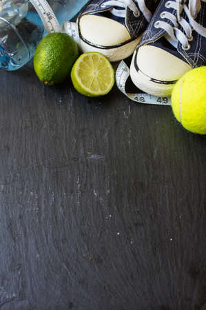 Sport shoes, measuring tape, lime and water on black