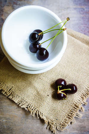 cereza: Cerezas maduras en la taza sobre la mesa viejo estilo r�stico