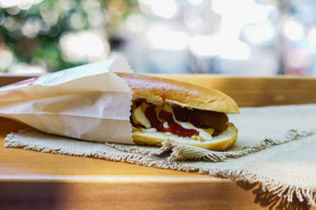 prepared food: hotdog with ketchup and mustard on wooden background
