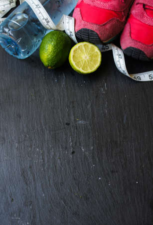 Sport shoes, measuring tape, lime and water on black background