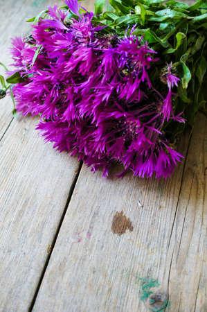 centaurea: cornflowers on the old wooden table, rustic