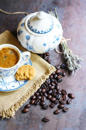 taza cafe: Vintage cup with black coffee, dry lavender flowers and coffee beans