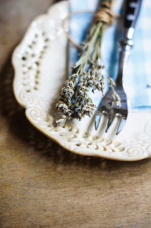 abbassa: Rustic Table Setting with napkin, silverware and dry lavendre lowers on old wooden table Archivio Fotografico