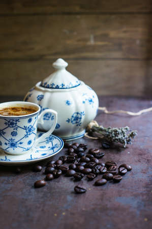 Vintage cup with black coffee, dry lavender flowers and coffee beans