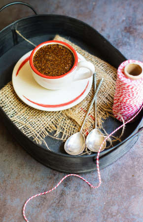 chritmas: coffee cup and bright red napkin with chritmas ribbon and spices on dark rustic background Stock Photo