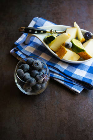 fruity salad: Fresh Organic Fruit Salad in a bowl with vintage spoon on the bright napkin