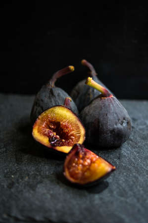 Ripe fig fruits on the dark vintage background. Selective focus
