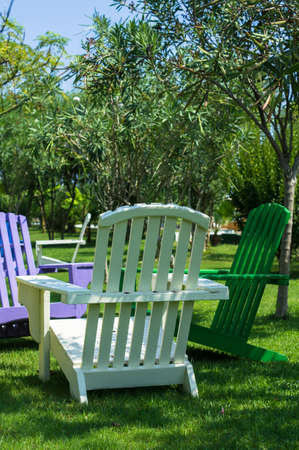 femal: Bright color wooden sun chairs in the beach garden