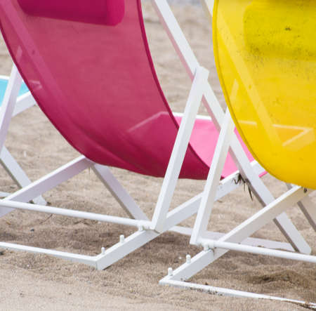 view on sea: Bright colors sun chairs on the sand beach of Mediterranean sea Stock Photo