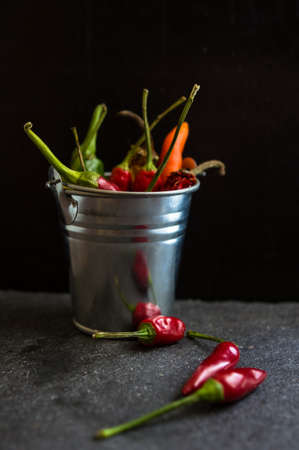 Spicy chili peppers on the black background. Selective focus