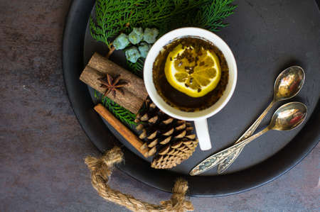 christmas tea: Mulled tea with spices and christmas decorations on wooden background