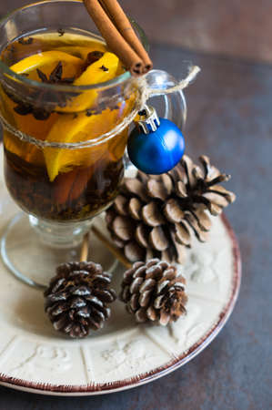 Mulled tea with spices and christmas decorations on wooden background