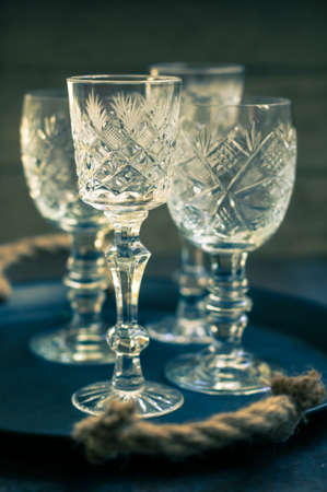 crystal glass: Vintage crystal glasses on the black tray with christmas decorations. Toned picture