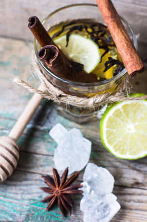 stimulated: Glass of tea with lemon, cinnamon and anise on the rustic background Stock Photo