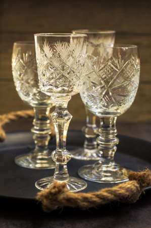 christmas party: Vintage crystal glasses on the black tray with christmas decorations. Toned picture