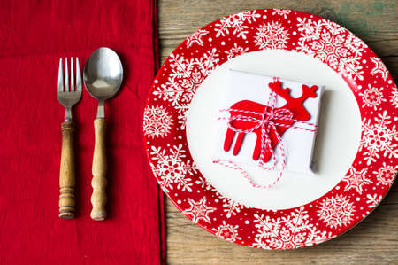 christmas party: Rustic christmas table setting with bright plates and silverware