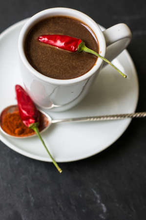 White cup with hot chocolate and spicy red chilli pepper Stockfoto