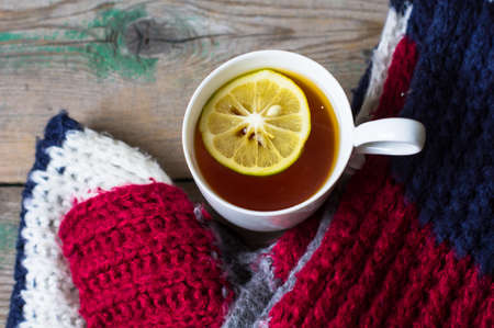 aansterken: Winter time: cup of hot tea with lemon and scarf on rustic background