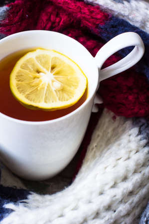 convalesce: Winter time: cup of hot tea with lemon and scarf on rustic background