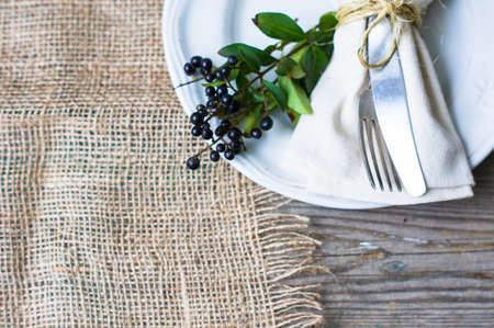colorful leaves: Rustic autumnal table setting with yellow leaves and berries Stock Photo